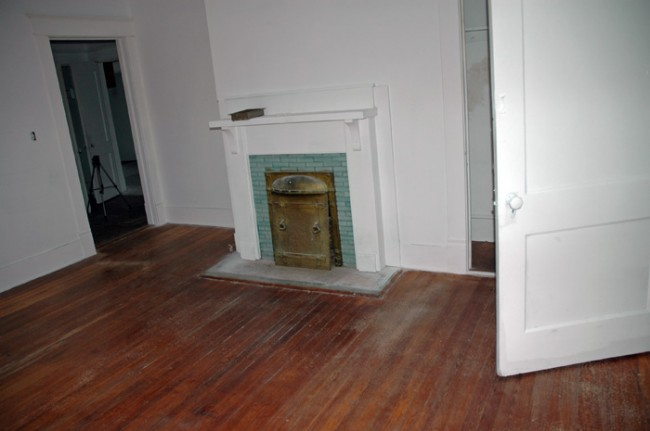 Door to hallway and coal fire place.